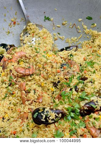 Big metal dish full of Spanish paella with mussels and prawn shrimps