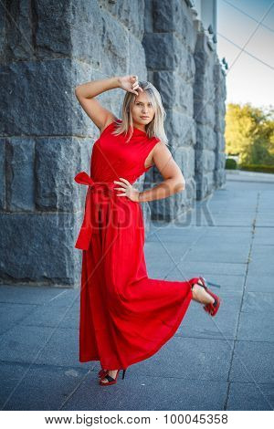 Beautiful Girl Posing In A Red Evening Dress In The Park Outdoors