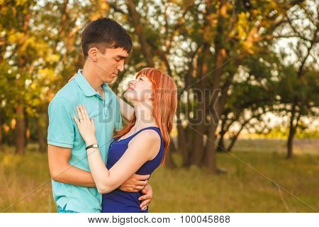 Young Couple Hugging In Forest Outdoors