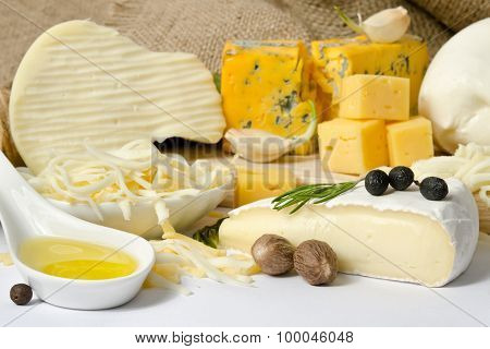 Various Types Of Cheese With Spice On The Wooden Board