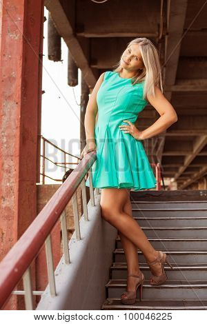 Beautiful Girl In A Turquoise Dress Posing On The Street; Outdoors.