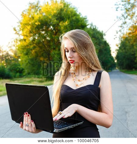 Young Beautiful Woman With Concentration Works With A Laptop On The Road
