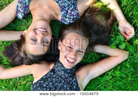 Two Female Friends Is Lying On Grass And Laughing
