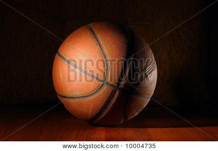 Basketball Ball In Dark On Wooden Floor
