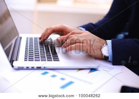 Businessman at a table with a smartphone and a laptop