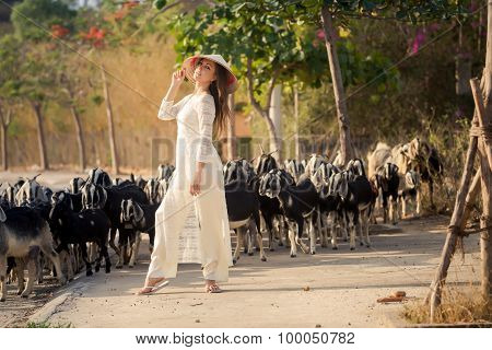 Blonde Girl In Vietnamese Dress Stands Against Flock