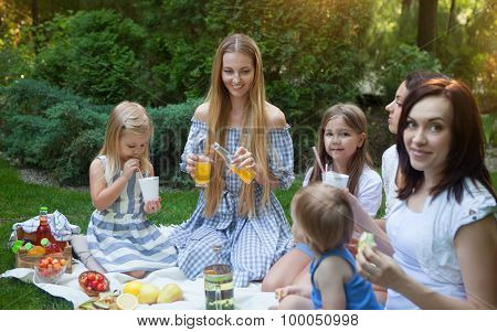Three Happy Young Mothers And Daughters Having Picnic