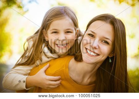 Two Cheerful Sisters Playing In The Park