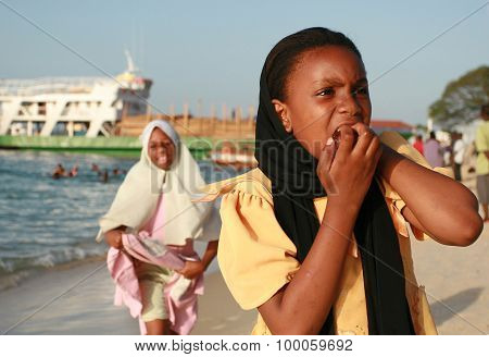Muslim Black Girl Walking On The Beach Near The Port Of Zanzibar.