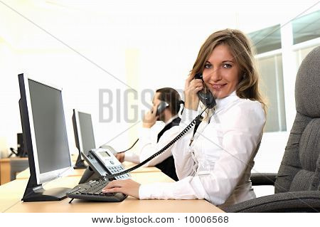 Young Girl At Office On The Workplace Makes Call