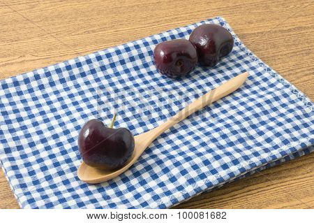 Red Plums On A Blue Checked Towel