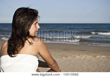 Beautiful girl with tattoo sitting on the beach