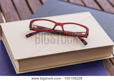 red eyeglasses on book