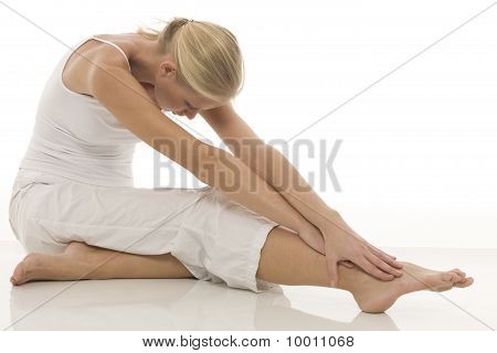 a young caucasian woman dressed in white sitting on the floor