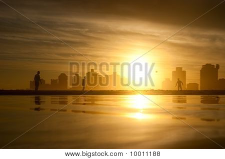 A Football Game On The Beach At Sunset
