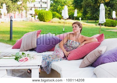 Lovely woman in summer dress sitting on sofa