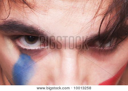 Eyes Of  Man With The Red And Blue Paint On His Face