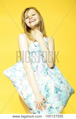 One beautiful young playful naked smiling woman with blonde hair holding big pillow in bright flower pattern pillow-case pastel colours standing on yellow studio background vertical picture poster