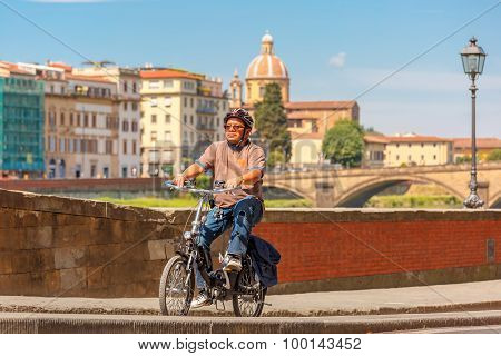 Cyclist on quay of river Arno in Florence, Italy