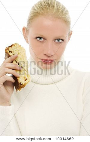 portrait of a young caucasian woman wearing a white turtleneck sweater and holding a slice of panett