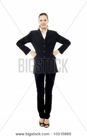 Young businesswoman standing with arms akimbo on white background studio