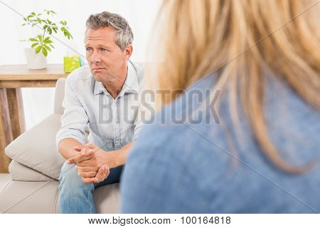 Worried man sitting on couch and talking to therapist in the office
