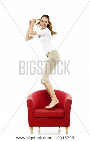 Young woman jumping on a chair on white background studio