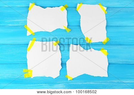 White pieces of paper attached on wooden background poster
