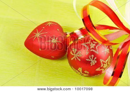 Two Christmas Balls On A Green Background