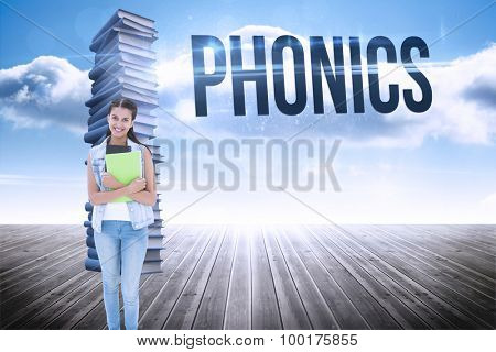 The word phonics and student holding notepads against stack of books against sky