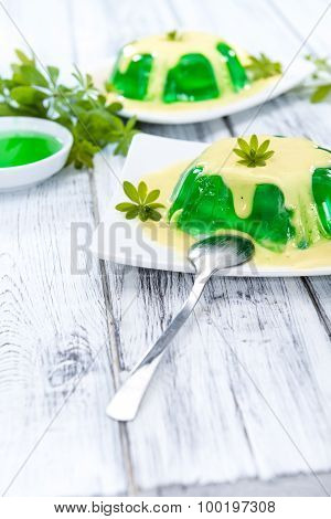 Woodruff Jelly with Vanilla Sauce (on wooden background) poster