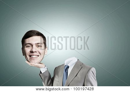Young headless businesman holding his head in palm