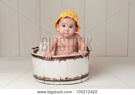Baby Girl Sitting In A Wooden Bucket