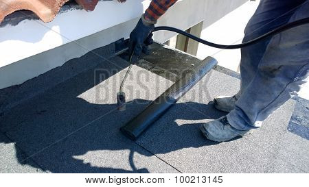 Roofer preparing part of bitumen roofing felt roll for melting by gas heater torch flame poster