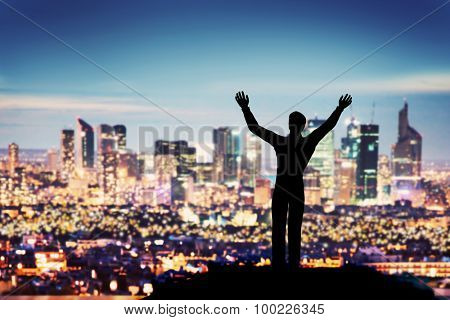 Successful businessman with hands up facing city business downtown at night. Concept of winner, corporate manager etc.
