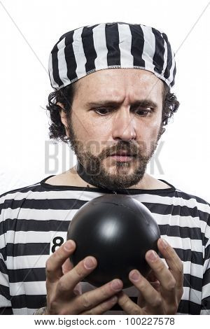 Funny man prisoner criminal with chain ball and handcuffs in studio isolated on white background