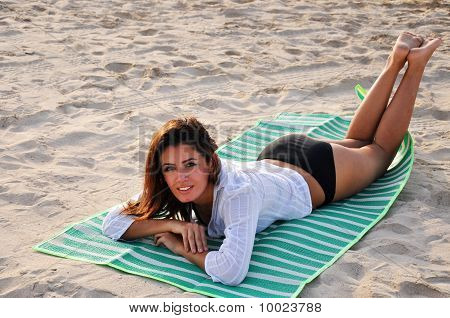 Young Smiling Woman Laying On Towel At The Beach