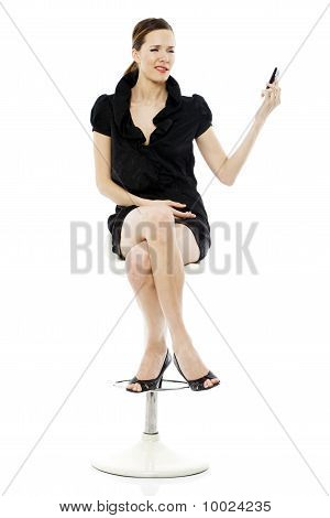 woman sitting on a stool holding a cellphone