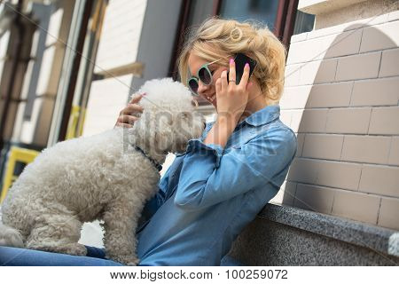 Cute blonde with Bichon Frise white dog