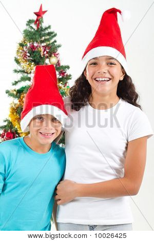 brother and sister wearing christmas hats