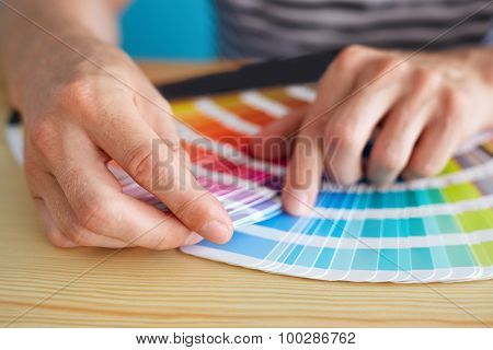 Graphic designer choosing a color from the sampler poster
