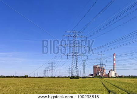 Electricity Pylons With Power A Station In The Middle Of A Agricultural Field
