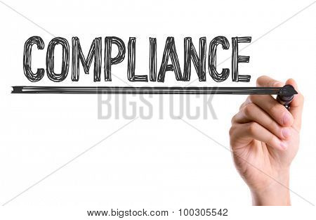 Hand with marker writing the word Compliance