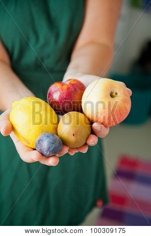 Woman Holding Many Different Fruits In Her Hand.