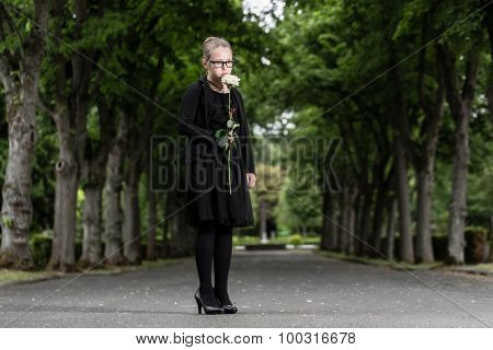 girl with white rose mourning deceased on graveyard being an orphan now