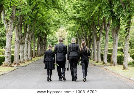 Family walking down alley at graveyard