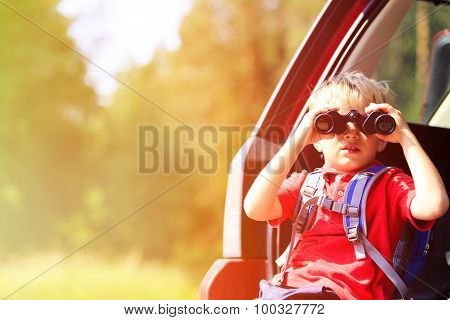 little boy looking through binoculars travel by car