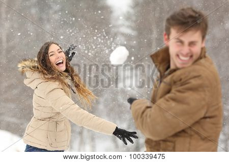 Couple Playing With Snow And Girlfriend Throwing A Ball