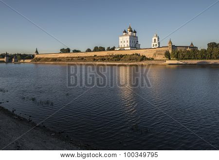 The City Of Pskov. Russia. Pskov Kremlin. Holy Trinity Cathedral and bell tower from the side of the Great river at sunset. poster