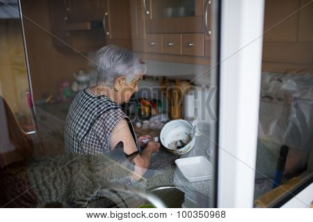 Elderly Woman In The Kitchen